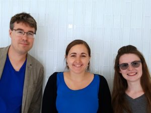 "Photograph of three people. the authors of the article ""watching the dust and clouds float lazily by during a martian summer."" On left is a mad, late-thirties to early forties, white with glasses. Two other people are young women in their early twenties, both white with dark hair."