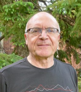 Photograph of Wayne Richardson, President of CMOS. Pictured is a man's head and shoulders. He is dressed in a t-shirt. He is in his early 60's, is balding, and is wearing glasses.