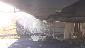 Image showing the moment of impact between a passenger vehicle and a transport truck, underneath a bridge.