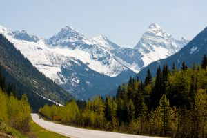 Highway through the Rogers Pass in the Canadian Rockies against a backdrop of forested hillsides and snow-capped mountain peaks.