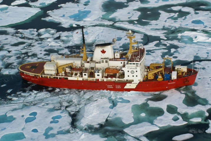 Aerial view of a large research vessel moving through icy waters