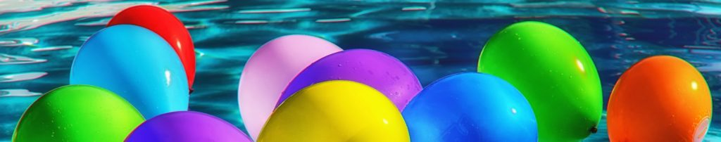 photo of birthday balloons floating in a swimming pool