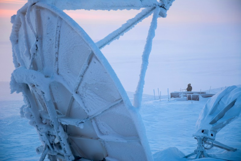 Photo shows a snow and ice covered satellite in the foreground, with a researcher in the background, near Eureka.