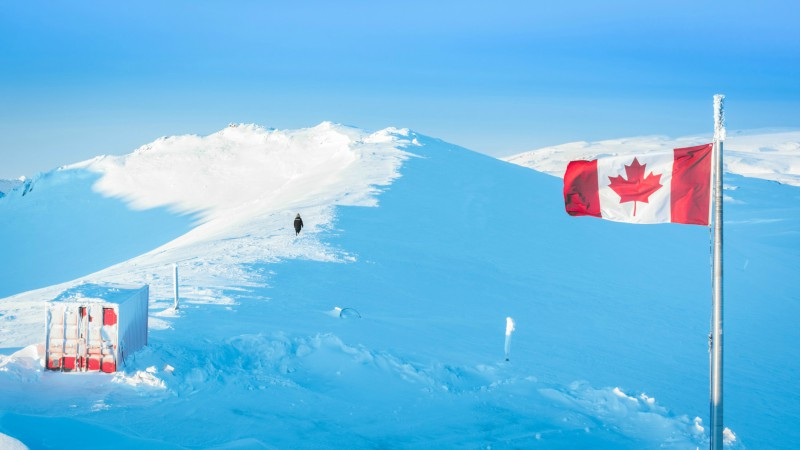 Photo shows a Canada flag waving in the foreground beside a building, and a person in the distance walking along a snowy ridge at the PEARL ridge lab at Eureka.