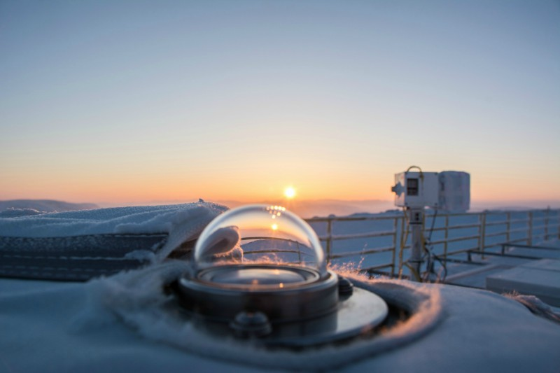 Photo shows a glass domed instrument on the rooftop at PEARL, Eureka, with the setting sun in the distance.