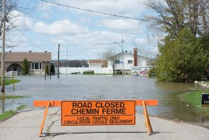 "Photo shows a ""road closed"" sign with a flooded town street in the background"