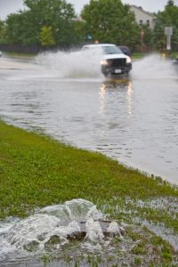 Photo shows a pickup truck driving through a flooded street.