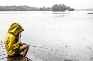 Photo shows a young girl in a yellow rain jacket with the hood up, sitting beside a lake.