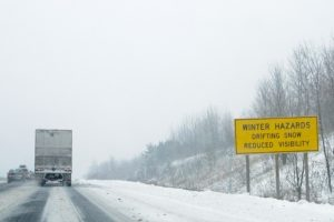 Photo shows a transport trailer driving along a snowy highway