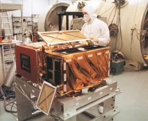The MOPITT instrument shown here as a square metallic box with an open lid, and a man in a white clean suit overseeing it, undergoing test at the University of Toronto around 1995.