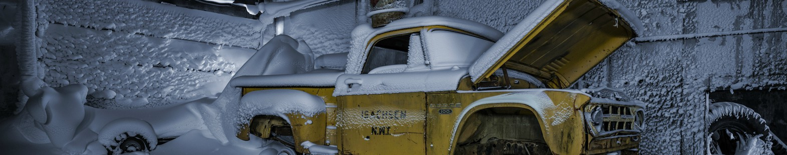 Image from Isachsen by aAron munson shows an old yellow truck, covered in snow, in a frozen garage.