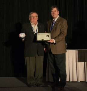 Two men, one handing the other an award. Paul Andre Bolduc is the recipient of a CMOS volunteer award