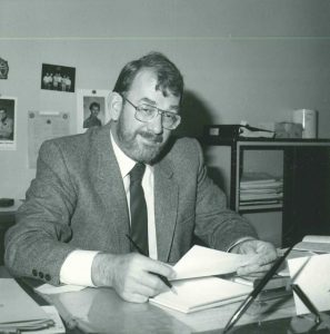 Black and white photo of Phil Merilees. Photo shows a caucasian man with eyeglasses and a beard, sitting at a desk. Circa 1975.