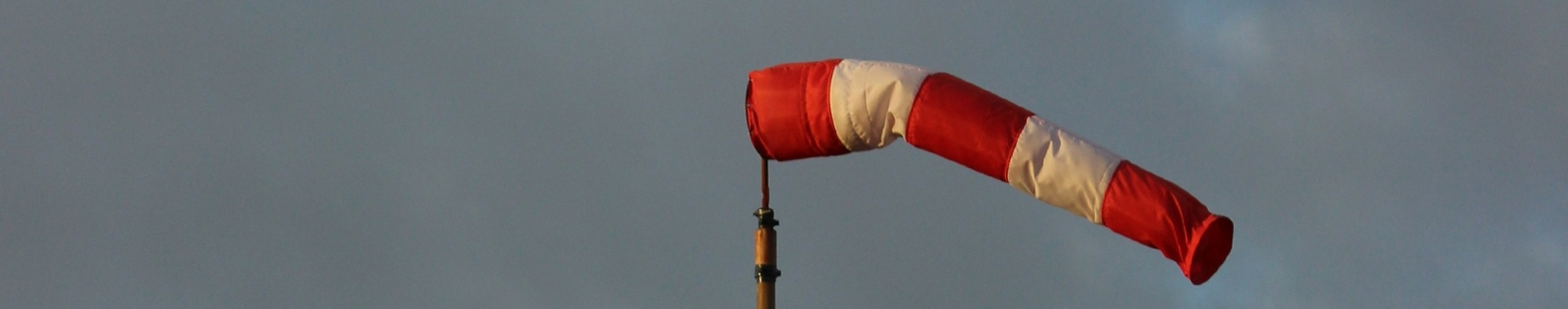 Image shows a red and white wind sock against a cloudy sky. Photo for the Wind at Lake Saint Charles article by Richard Leduc
