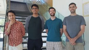 Photograph showing four young men, smiling, wearing summer clothes. They are part of the Moore group and authors of The Lunar Atmosphere