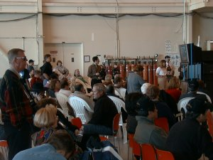 Photo of a room full of people, seated and standing, all looking the same direction for the MOPITT launch