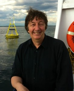 Smiling caucasian middle aged man with dark hair, standing on a boat at sea, leaning on the rail, with a yellow buoy in the background