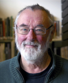Caucasian senior male with white beard and mustache, with glasses, smiling, and books in the background