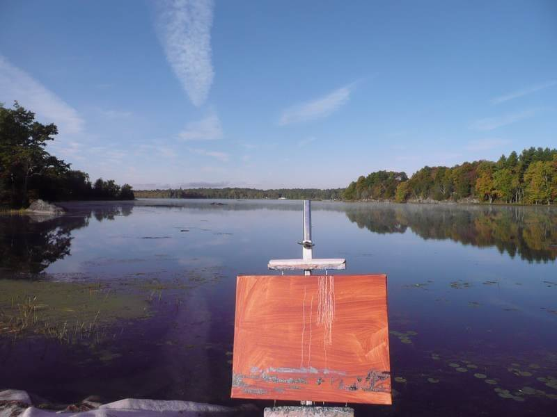 Red base canvas on an easel by a lake an blue skies with clous overhead