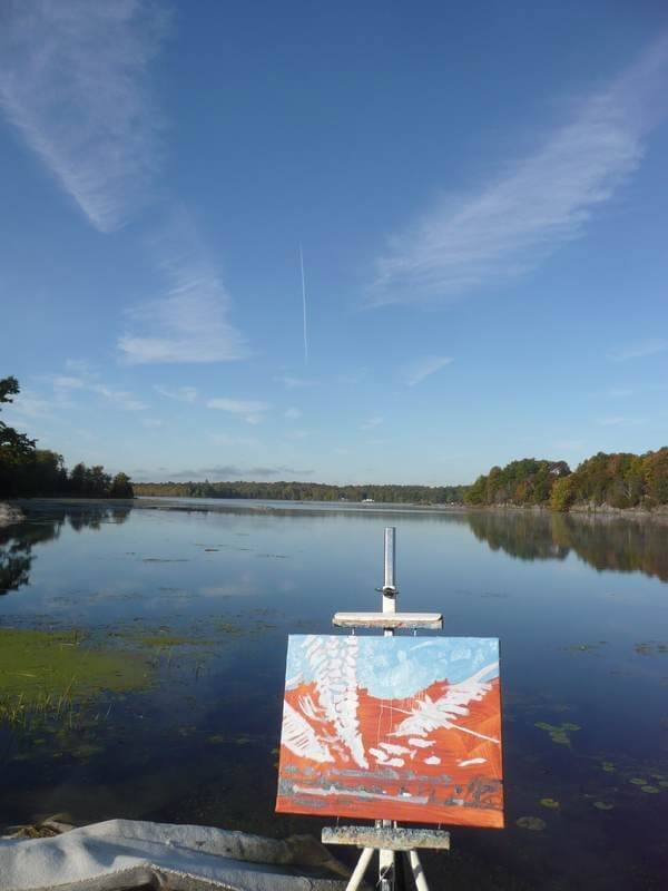 landscape painting in progress on canvas on an easel by the lake. Painting is red, with white marks and blue sky
