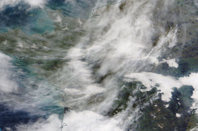 satellite image of land and sea, and white whispy contrails