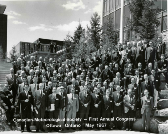 black and white photo of dozens of men in suits in front of a building at CMOS's first Congress in 1967