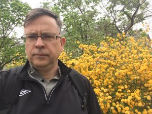 Caucasian man with glasses in a black jacket in front of yellow flowers